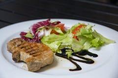 Steak mit Salat auf dem Tisch Stockfotos