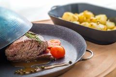 Steak mit Tomaten und Ofenkartoffeln, Abendessenlebensmittel, Restaurant Lizenzfreies Stockbild