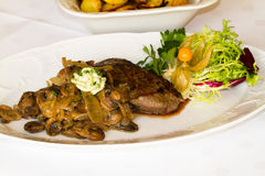Steak with mushrooms and potatoes. In a restaurant Stock Photos