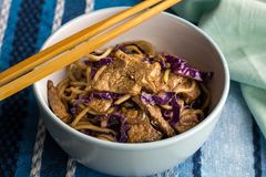 Steak, noodles and purple cabbage closeup in bowl with chopstick royalty free stock images