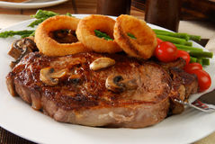 Steak and onion rings. A grilled rib steak topped with onion rings Stock Photos