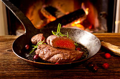 Steak in Pan with Chimney Fire. Steak in a pan with wine as closeup in front of a chimney fire Royalty Free Stock Photo