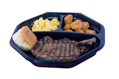 Steak picnic lunch. Cooked steak picnic lunch in plastic tray with bread bun isolated on white background Royalty Free Stock Photos