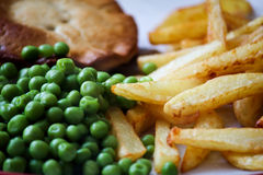 STEAK PIE CHIPS AND PEAS. STEAK PIE CHIPS WITH PEAS ON A PLATE READY FOR EATING Stock Image