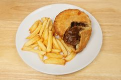 Steak pie and chips. On a plate ona wooden tabletop royalty free stock photography