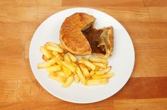 Steak pie and chips on a tabletop. Steak pie and chips on a plate on a wooden tabletop Royalty Free Stock Photography