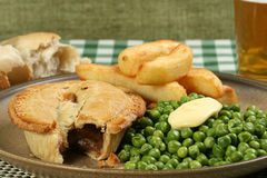 Steak pie with fries and peas Stock Images