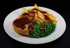 Steak Pie, fries, peas and gravy. Close up of Steak Pie and fries with peas and gravy. A traditional British Dish Royalty Free Stock Photos