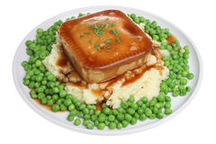 Steak Pie, Mash & Peas. Steak pie on a bed of mashed potato with peas and gravy Royalty Free Stock Photo