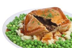 Steak Pie, Mash & Peas. Steak pie with mashed potato, peas and gravy Royalty Free Stock Photography