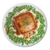 Steak Pie, Mash & Peas. Steak pie on a bed on mashed potato with peas and gravy Royalty Free Stock Photo