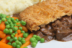 Steak Pie, Mash & Vegetables. Top-crust steak pie with mashed potatoes, peas and carrots Stock Image