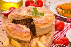 Steak pie. Steak pie with carrots, peas and french fries stock photo