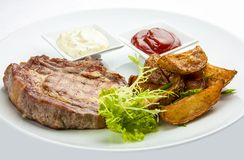 Steak from pork chop with potatoes on a white plate royalty free stock photos