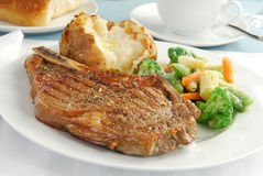Steak and potato. A grilled rib eye steak with a baked potato stock images