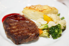 Steak with potato au gratin and vegetables Stock Images