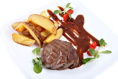 Steak with potato slices on flat dish, isolated on white Royalty Free Stock Images
