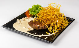 Steak with potato straw in mushroom sauce Stock Photo