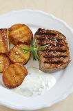 Steak with potato wedges Stock Photos