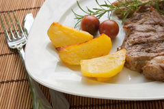 Steak with potatoes and cherry tomatoes Royalty Free Stock Images