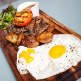 Steak with potatoes and eggs Royalty Free Stock Image