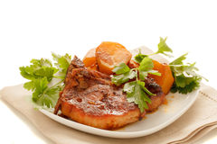 Steak with potatoes on a plate. Pork steak with potatoes seasoned with parsley on a plate on a white background royalty free stock image