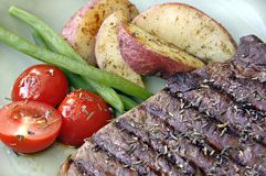 Steak with Potatoes, Tomatoes, and Beans Royalty Free Stock Photo