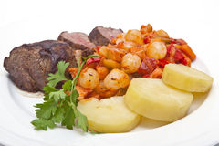 Steak, potatoes and vegetables Stock Photos