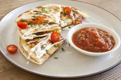 Steak Quesadilla with Salsa and Sour Cream. Shot on a wooden table royalty free stock image