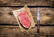 Steak raw meat with a knife. On wooden background. Steak raw meat with a knife. On the wooden background. Top view Royalty Free Stock Images