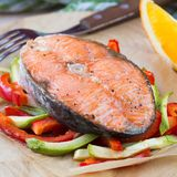 Steak red fish salmon on vegetables, zucchini, sweet pepper Stock Photo