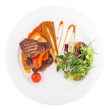 Steak rib-eye garnished with grilled vegetables. Isolated on white background Stock Photography