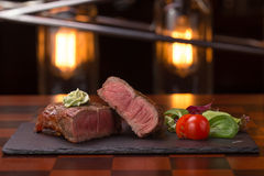 Steak rib-eye. Garnished with grilled vegetables on stone plate Stock Photo