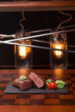Steak rib-eye. Garnished with grilled vegetables on stone plate Royalty Free Stock Images