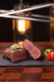 Steak rib-eye. Garnished with grilled vegetables on stone plate Stock Image