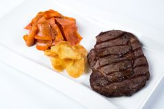 Steak rib-eye garnished with grilled vegetables on Royalty Free Stock Photography