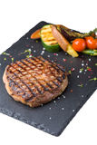 Steak rib-eye with grilled vegetables. Served on a stone plate isolated on white background Stock Photography