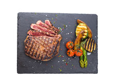 Steak rib-eye with grilled vegetables. Served on a stone plate isolated on white background Royalty Free Stock Images