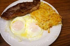 Steak ribs with two eggs over easy and Hash-brown potatoes Stock Images