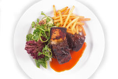 Steak ribs, vegetables salad and french fries. On white background Stock Image