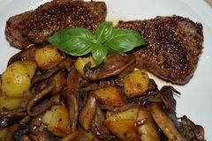 Steak with roasted mushroom, onions and potatoes. Steaks in a frying pan Royalty Free Stock Photo