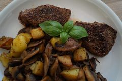 Steak with roasted mushroom, onions and potatoes. Steaks in a frying pan Royalty Free Stock Photography