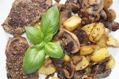 Steak with roasted mushroom, onions and potatoes stock photos