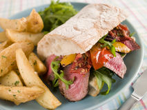 Steak and Roasted Pepper Ciabatta Sandwich. Plate of Steak and Roasted Pepper Ciabatta Sandwich with Spiced Potato Wedges stock photos