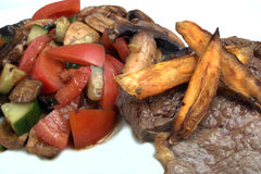 Steak and salad. Steak with sweet potato chips and tomato salad Royalty Free Stock Photo