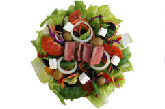 Steak Salad. A salad with steak, lettuce, red pepper, yellow pepper, carrots, onion, tomatoes, black olives, green olives, parsley, red cabbage, feta cheese Stock Images