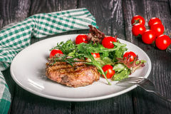 Steak and salad. Closeup of barbecued steak and salad of cherry tomatoes and rocket on white china plate, all on a dark wooden table with extra tomatoes beside Royalty Free Stock Photo
