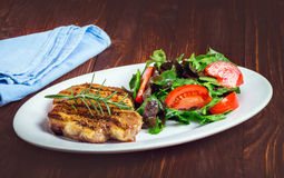 Steak and salad on a plate. Fried steak on the plate with salad and vegetables Royalty Free Stock Photos