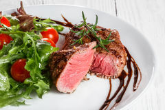 Steak and salad on a plate. Fried steak on the plate with salad and vegetables Royalty Free Stock Photo