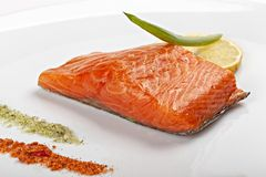 Steak of salmon with lemon on  white plate. royalty free stock images